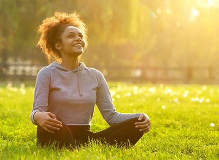 Happy woman sitting in field